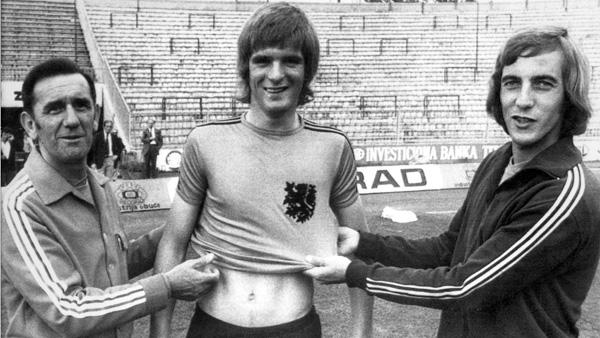 Heini Otto wordt in het Oranjeshirt gehesen door bondscoach George Knobel en Johan Neeskens.